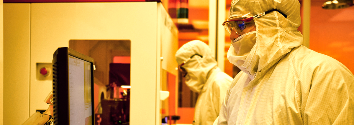 Photo of two people in clean room garb working on a machine tool.
